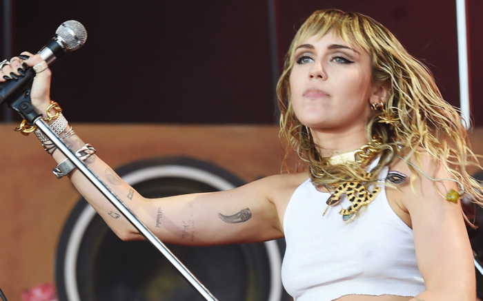 Miley Cyrus Takes the Stage in a Graphic Tee, Short Shorts & Metallic Go-Go Boots at Lollapalooza